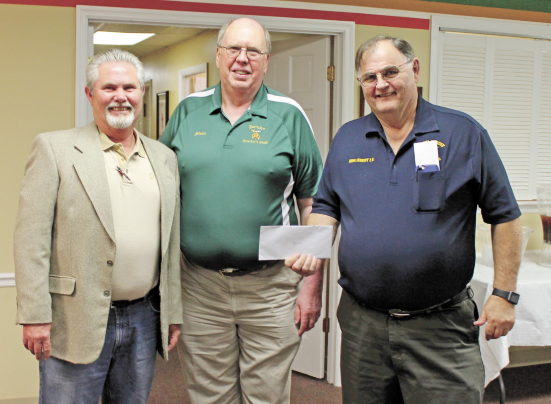 Lou Snider, left, presents a donation on behalf of his business, Hawg-N-Dawg, to Shriners Steve Gryder, center, and Herb Kennedy. (Erwin Record Staff Photo by David Sheets)