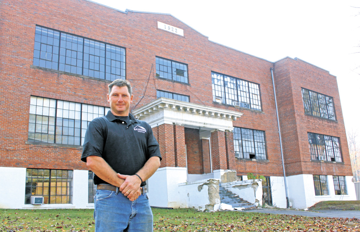 Lee Naylor stands in front of the old Elm Street school building. Naylor has agreed to purchase the property and hopes to renovate the building into a residential development. (Erwin Record Staff Photo by Keith Whitson)