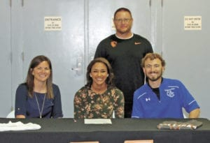 Lady Devil senior Stephanie Wisse, seated center, signed with Milligan College last week. Pictured with Wisse are head UCHS track coach Megan Davis, assistant UCHS coach Thad Higgins, seated, and Milligan coach Jeremy Clonce. (Erwin Record Staff Photo by Keeli Parkey)