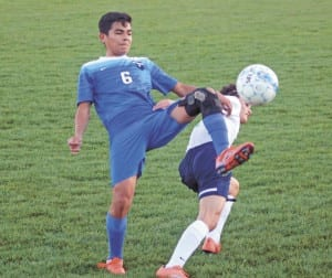 Blue Devil Daniel Meza fights for possession of the ball against a University High Jr. Buccaneer during his team's 5-2 victory last week. Meza scored a goal during the first half of play. (Erwin Record Staff Photo by Curtis Carden)